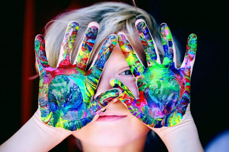 Boy covering his face with hands covered in multicolor paint