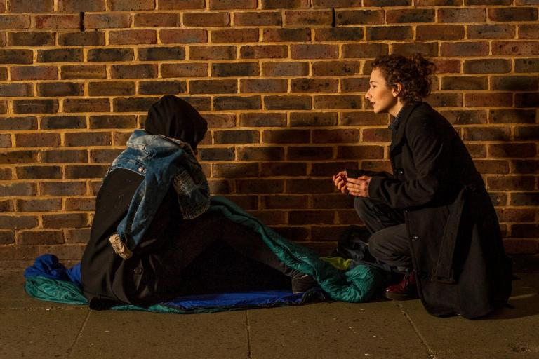 Image of a homeless man sitting on the ground talking to a support worker