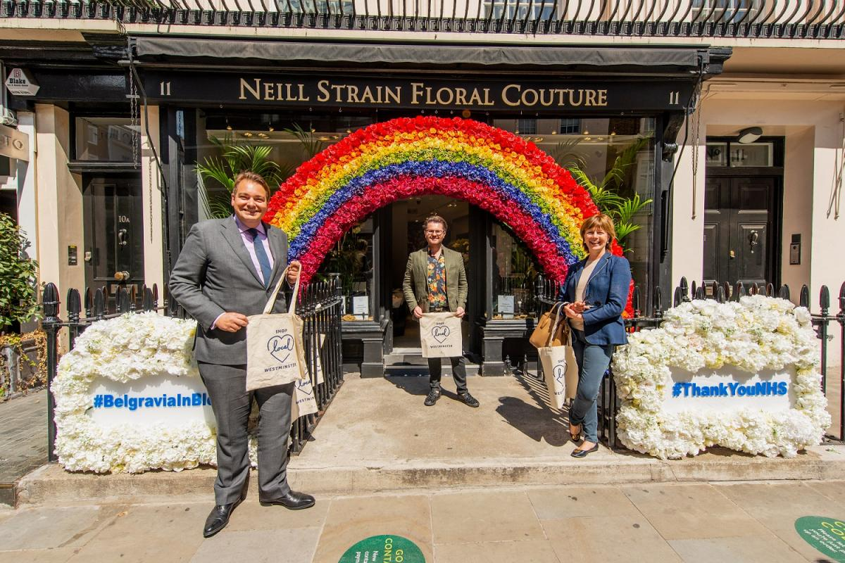 Westminster councillors pose for a photo under a rainbow arch outside a local shop.